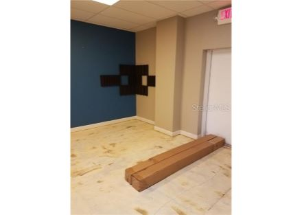 multipurpose back room, left wall to back door.  Room is approximately 17 ft by 19 ft.